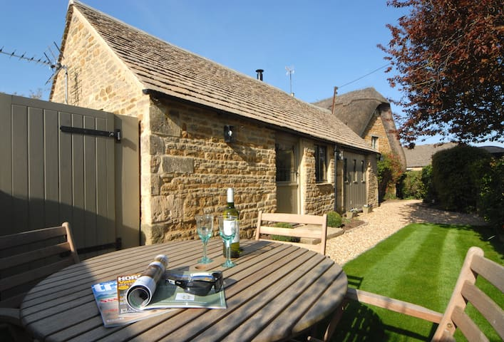 At the front of the property, there is an enclosed garden with lawn area, outside table and seating for four