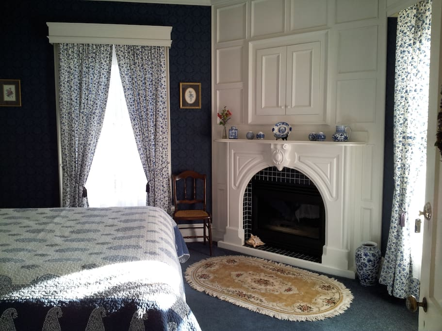 """Decorated in soothing blues & whites, everything about this room says, """"Ee comfortable and feel welcomed"""". In the room you'll find a comfortable wing chair, white paneling over the queen bed, and the original fireplace. The private bathroom is appointed with a double sized whirlpool tub that has a relaxing waterfall faucet. The bath also boasts a separate oversized marble tiled shower with double spa showerheads. All of our rooms offer cable TV and wireless internet."""