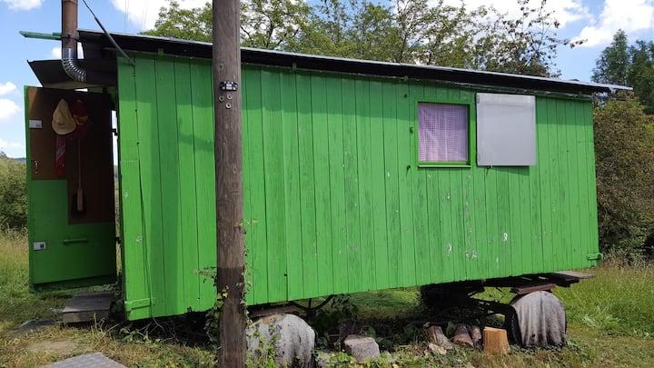 Wohnwagen in der Natur bei fröhlicher Familie