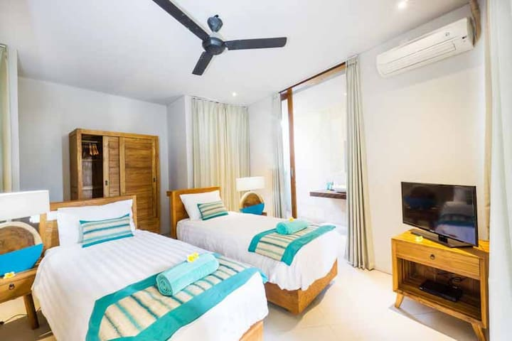 This is the ground floor 2 single bed bedroom equipped with AC, safety box, mini bar, water dispenser, a kettle with complimentary tea/coffee.