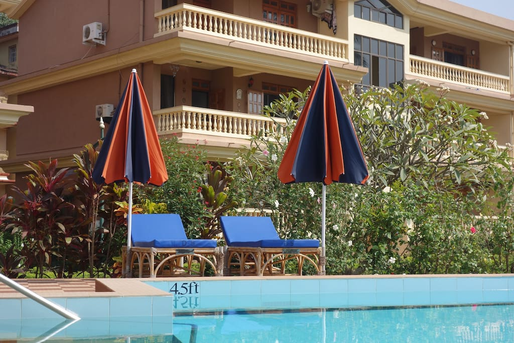 Private pool chairs with umbrellas