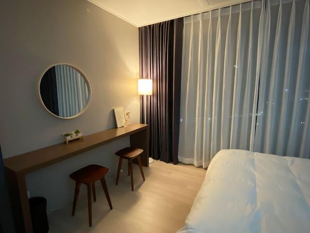 침실 내부입니다. 깔끔하고 따뜻한 느낌의 우드톤과 노란 조명을 통해 아늑한 느낌이 드는 모습입니다.