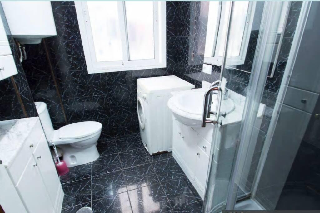 baño completo con mampara de ducha y lavadora