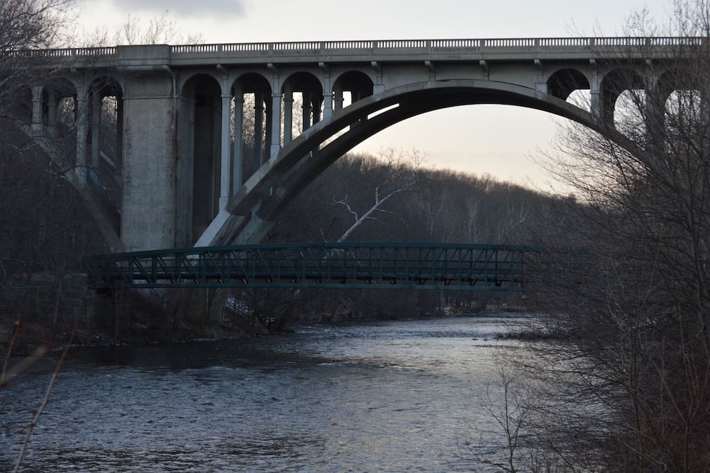 Charming pedestrian footbridge below historic Blackstone River bridge built earlier 20th century