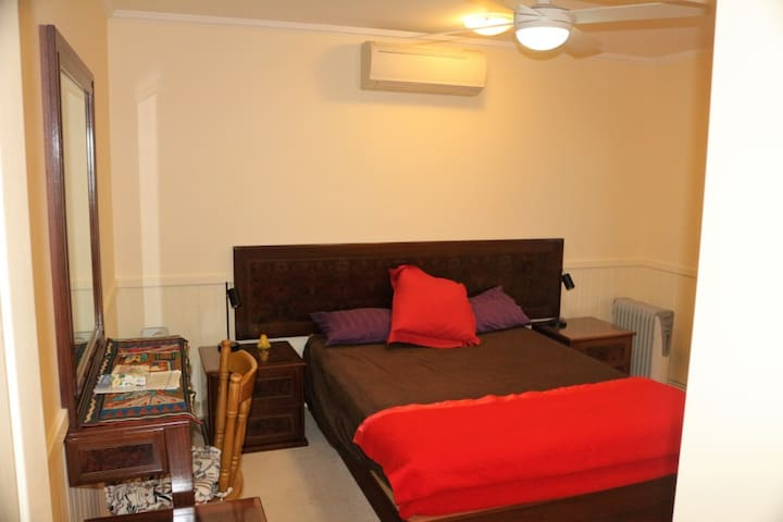 The bedroom with a small writing table, and cupboard to the right.  It has a fan light and air conditioning.