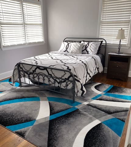 Master bedroom with queen bed, clock, walk-in closet, ceiling fan, and private bathroom with shower