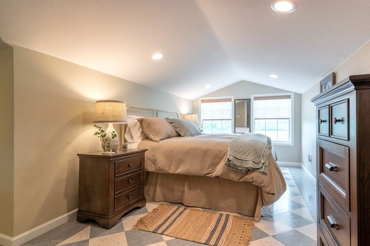 BEDROOM ONE: king bed, dresser, two night stands, bench, two mirrors, and ample closet space.