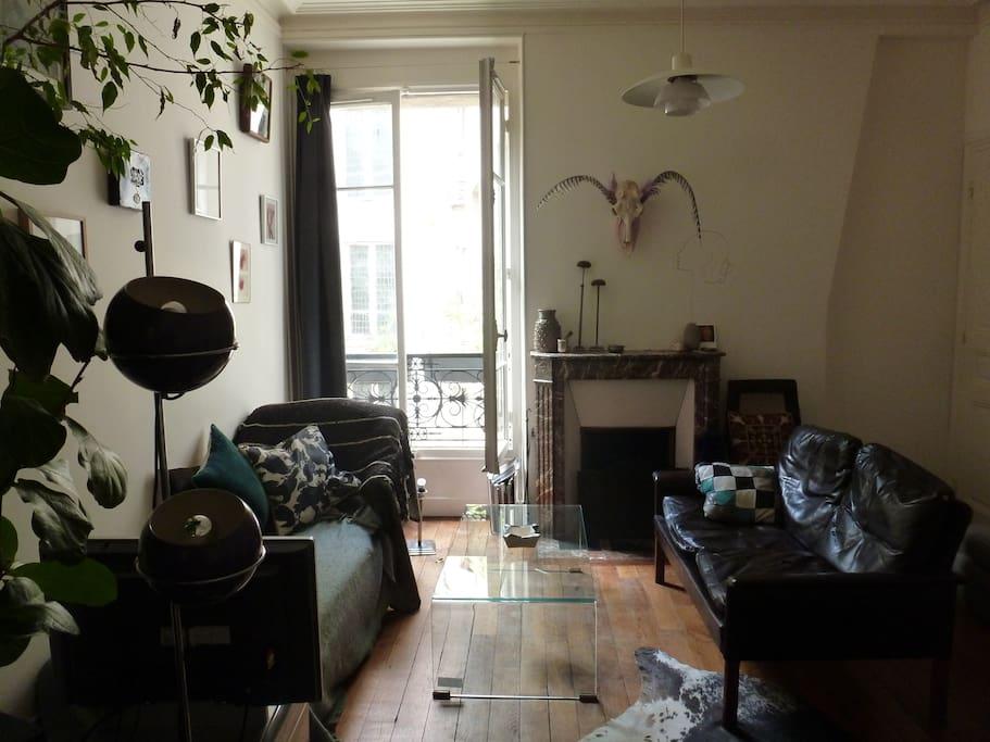 Salon: cheminée, canapés, grande fenêtre...