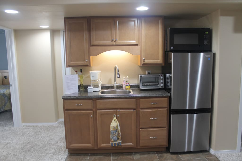 Kitchenette with refrigerator, freezer, microwave, toaster oven, 2 stovetop burners, basic coffee maker, pots/pans, dishes, silverware, etc.