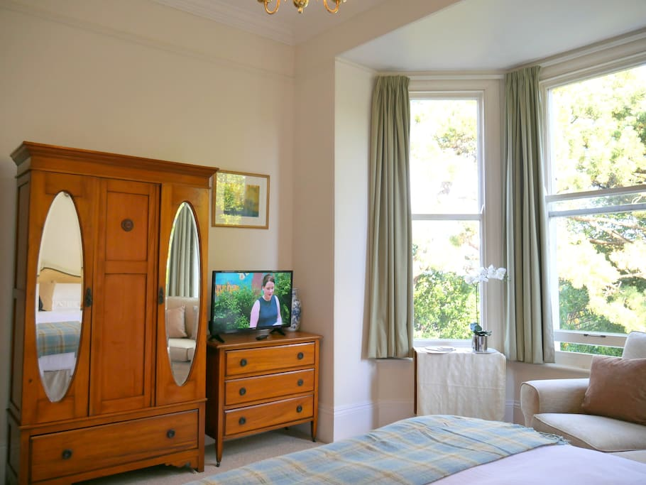 Spacious studio with luxury king sized bed, sofa, dining table and chairs plus antique walnut bedroom furniture