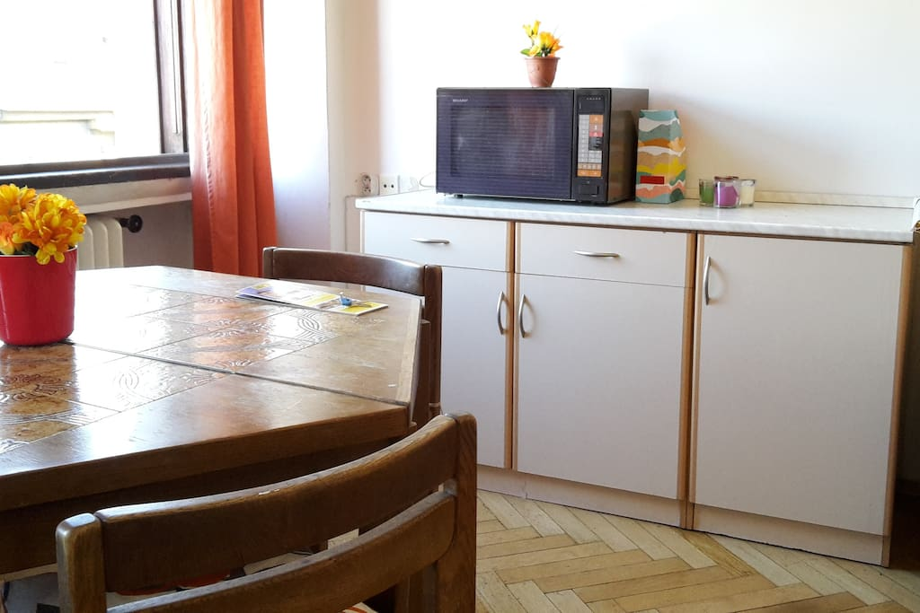 On this wall there is a kitchen counter with a microwave and cooking equipment and kitchenware. Large table in the middle of the room.