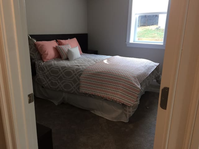 Bright light in bedroom, facing private side yard.  There are blinds on the window,, a spacious walk-in closet, side tables with drawers, and a nice bench for shoes and other items you want to have close by.  Door from bedroom to bath.