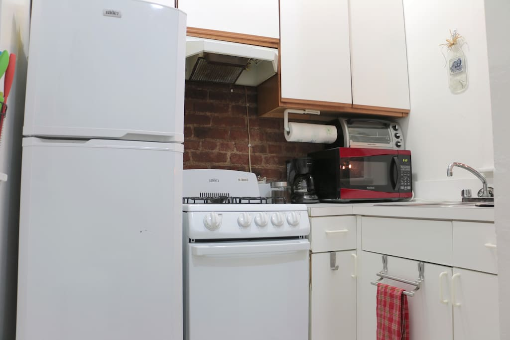 Kitchen with coffee, microwave, fridge, toaster, stove and oven.