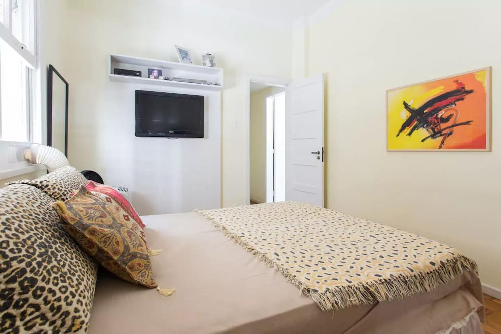 Quarto claro e aconchegante com cama de casal, televisão e ar condicionado.