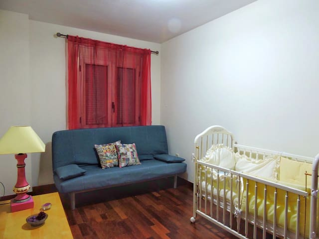 Tercera habitación con sofá cama y cuna