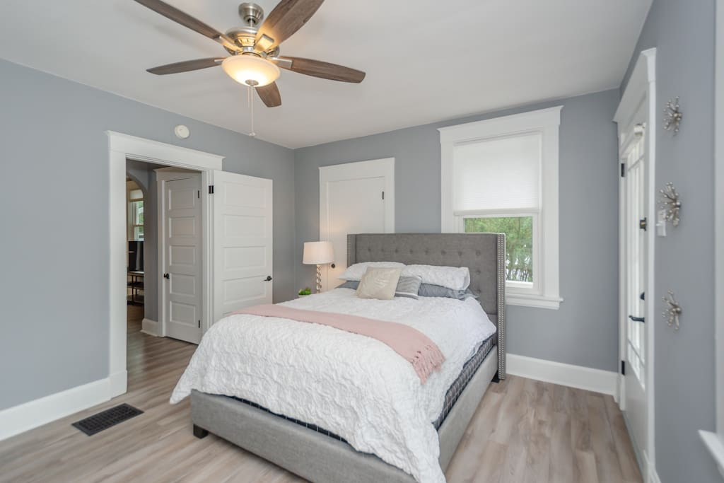 Master bedroom with natural light and door to outside balcony.