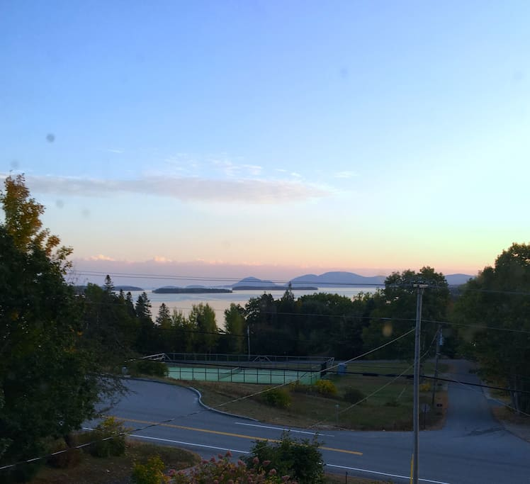 View from driveway of scenic turnout, tennis court, Frenchman Bay, Cadillac Mountain, and Bar Harbor.