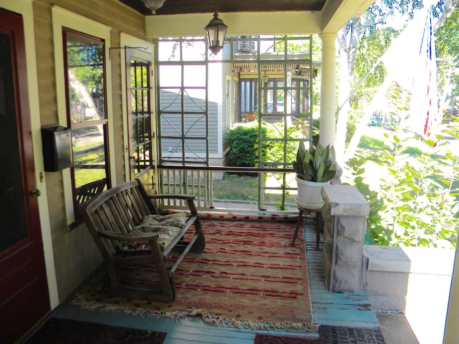 Large comfortable front porch with glider bench and space for table and chairs.