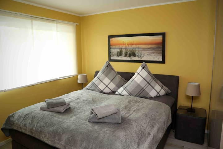 Schlafzimmer mit großem Kleiderschrank. Ein größerer Fernseher auf dem gegenüberliegendem Regal ist auch vorhanden.