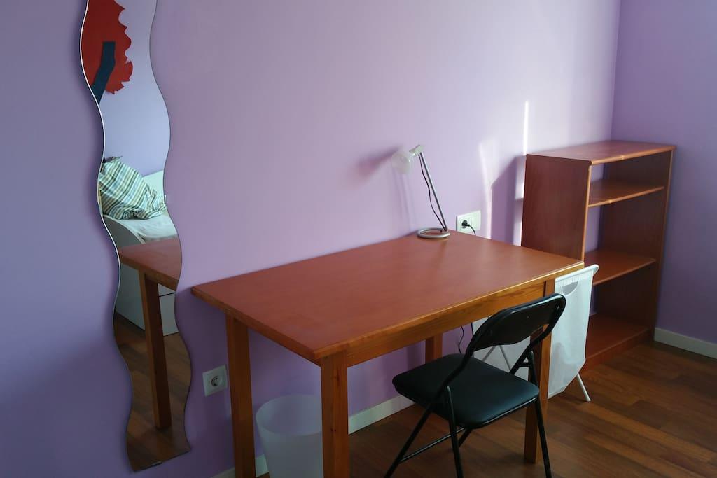estantería, mesa de trabajo con flexo y espejo en la habitación