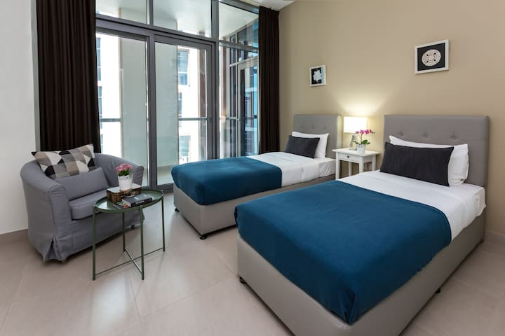 The second room includes two single beds and access to the balcony