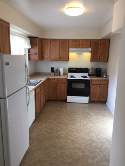 Full kitchen: stove, refrigerator, dishwasher, double sink, toaster, microwave, bottled water dispenser, coffeemaker, coffee, sugar, creamer, pots and pans, dishes, glasses, wine glasses,flatware, dish towels and pot holders