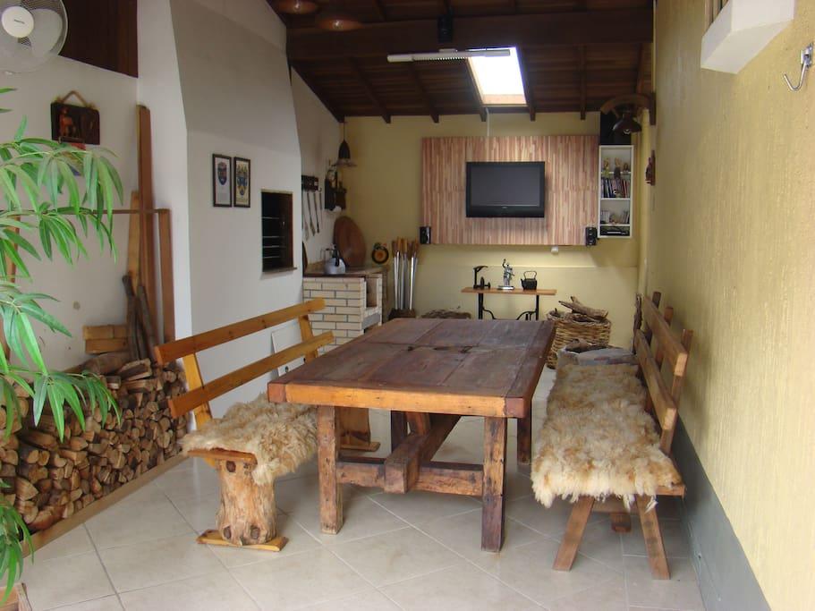 Garagem coberta com mesa, churrasqueira e televisão com DVD.