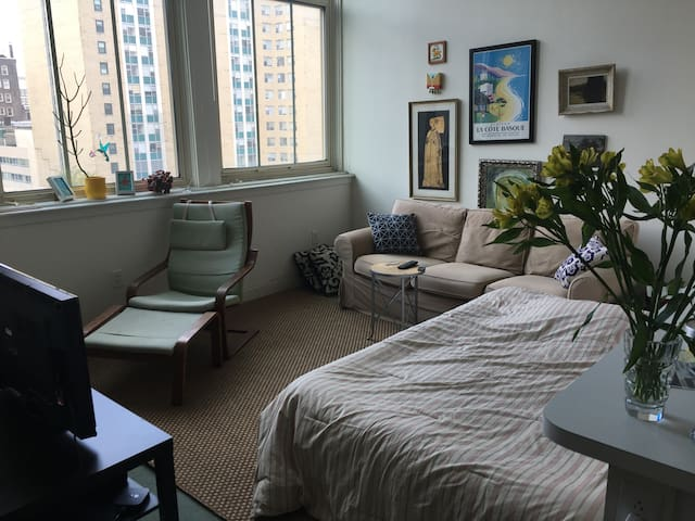 Room with sofa and queen sized bed.