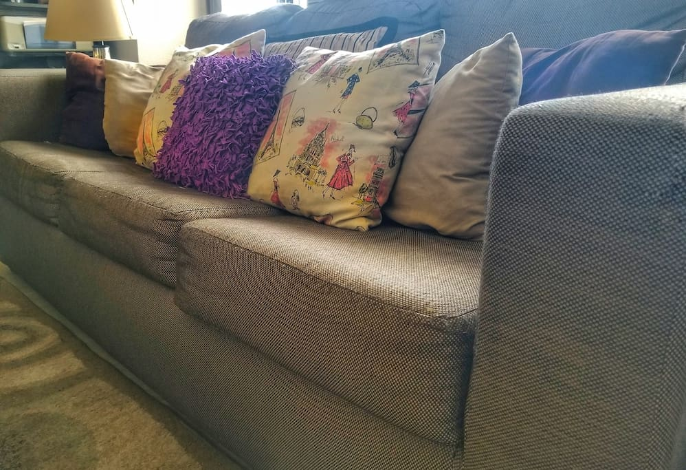 Pull out couch with queen size bed has plenty of pillows, blankets and a set of sheets in this chic, downtown Denver condo.