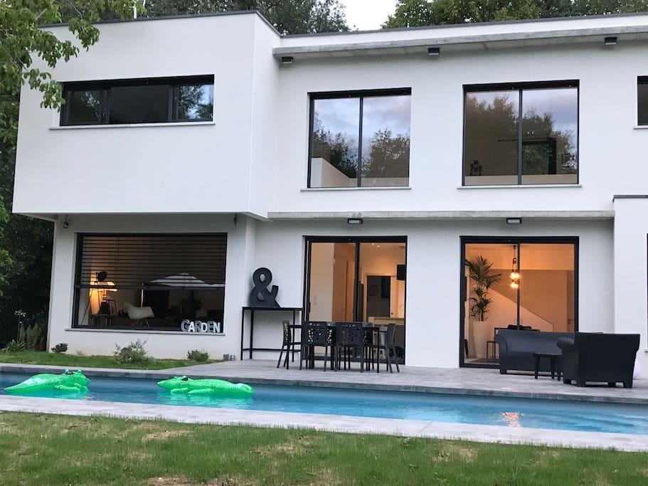 Maison côté terrasse et piscine avec 2 grandes baies vitrées pour profiter de l'intérieur avec la cuisine et de l'extérieur