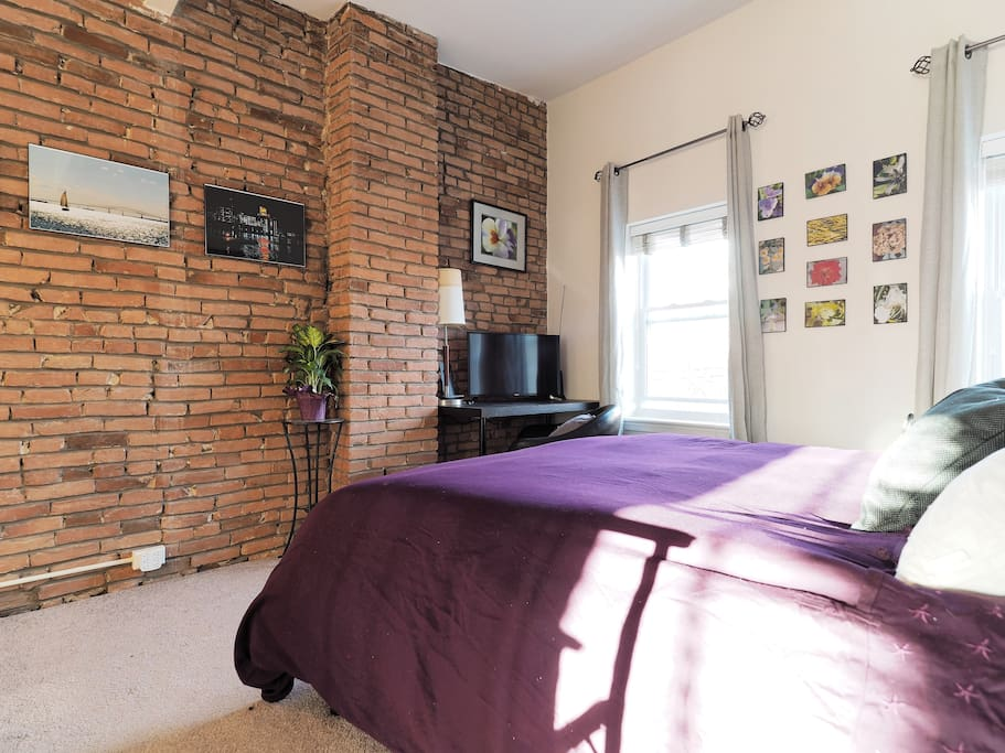 Master bedroom has gorgeous exposed turn-of-the-century brick- with all the modern comforts!