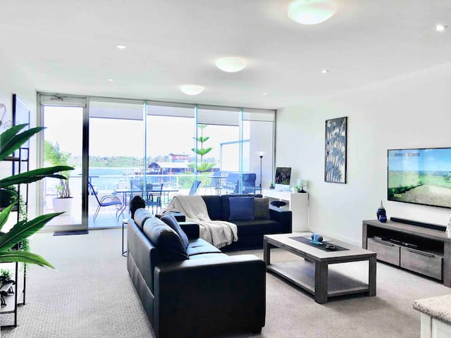 """Wall Mounted 58"""" 4K HD Television with Samsung Surround Sound Bar Balcony access from Lounge area for a Magnificent view of the Harbour"""