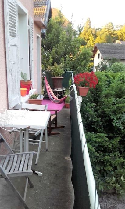 Balcon arrière ensoleillé jusqu'à 16h avec hamac, table et chaises.