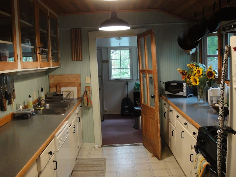 The galley-style kitchen is now maroon-and-white.