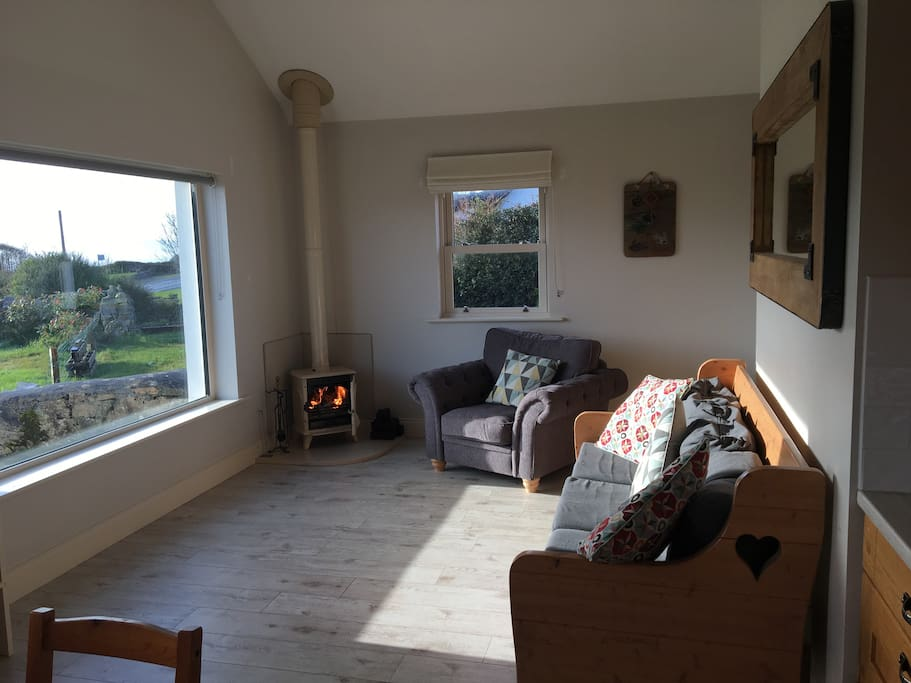 Snuggle up on our comfy sofa or armchair near the turf and log burning stove and enjoy the garden and sea views.