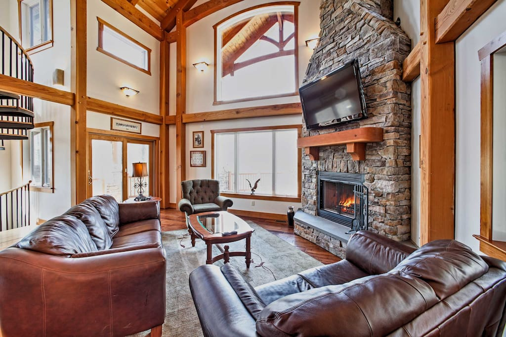 Soaring ceilings, gorgeous wooden beams, and a stunning stone fireplace adorn the cozy living room.