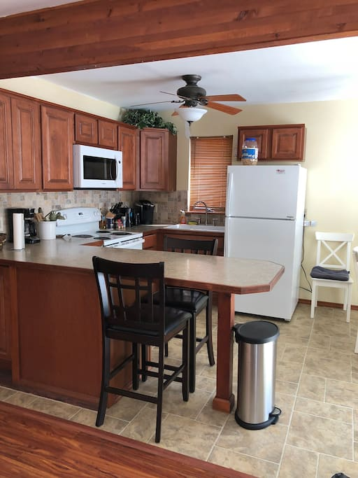 Modern kitchen with brand new appliances, including refrigerator, dish washer, range and microwave. Completed with coffee maker, kettle, double sink and breakfast bar.