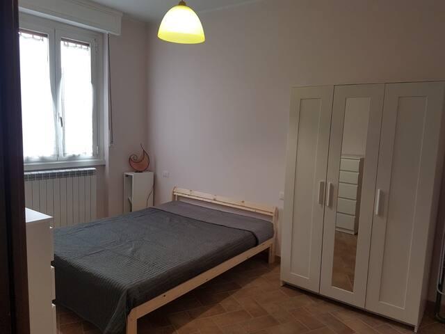 camera da letto con letto matrimoniale, armadio, cassettiera e libreria.