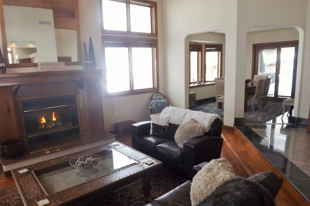 Gas fireplace in living room with granite and wood floors throughout the house.