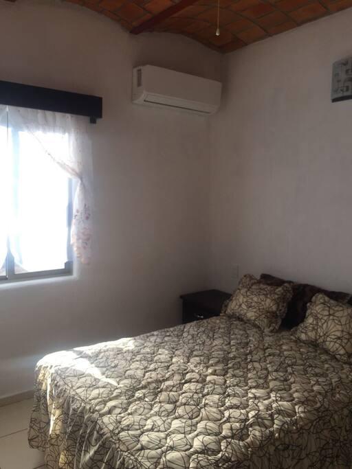 recamara con una cama matrimonial, ventilador y aire acondicionado.