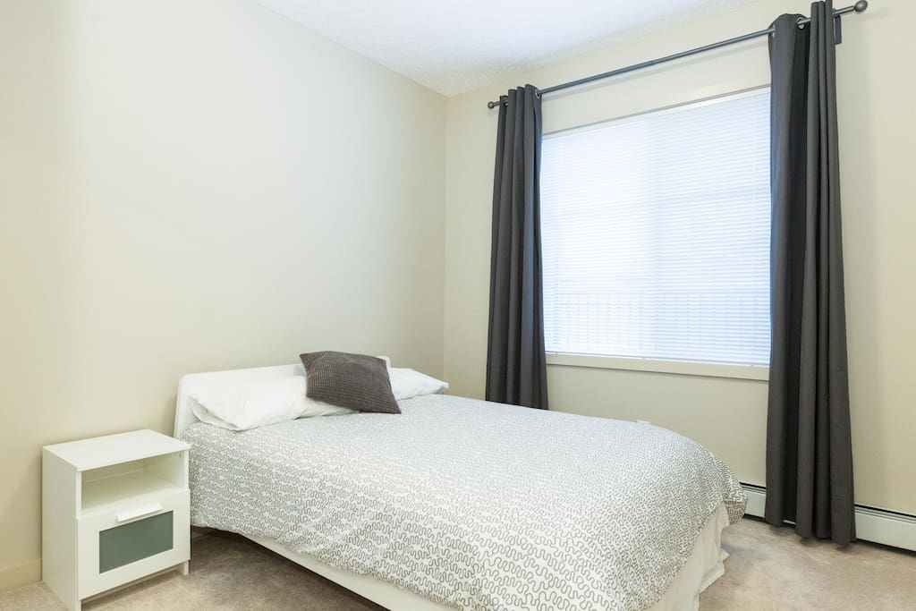 Guest room features new bed, large window overlooking balcony, and full mirrored closet.