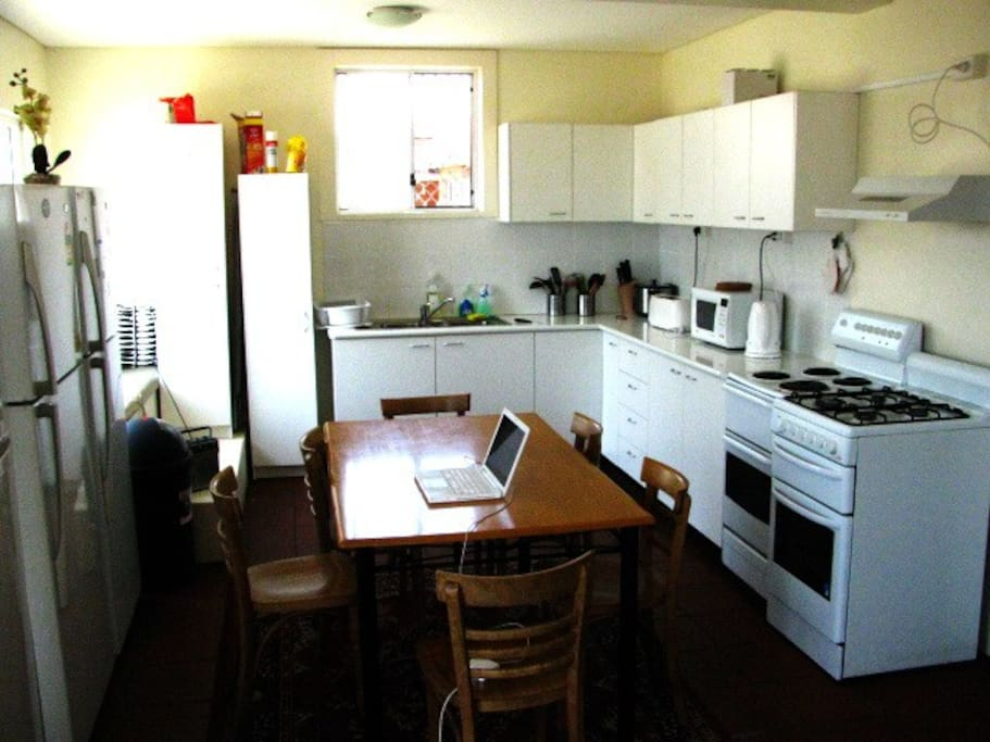 Large common kitchen with 3 fridges and 2 stove tops