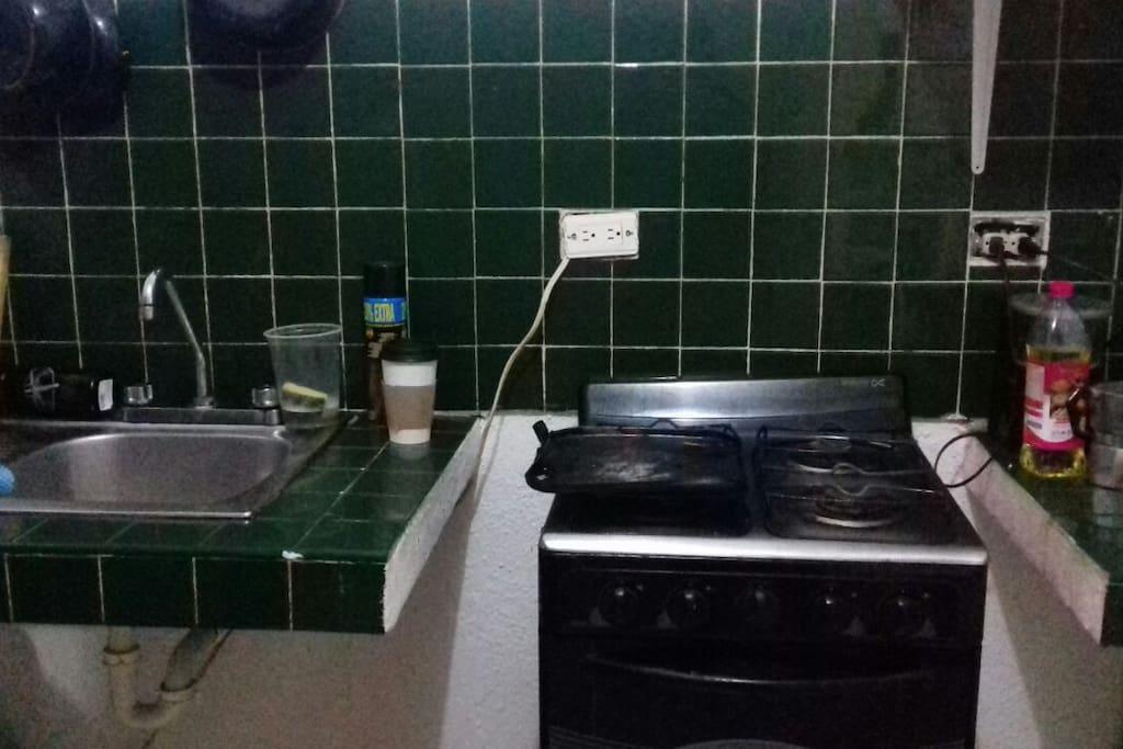 Cocina con estufa, lavadero y barra. Kitchen with stove, sink and bar.