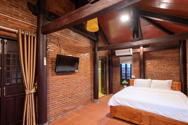 Room with 2 color tones: orange and brown, was designed in Vietnamese traditional style- brick and wood and use all-wooden interiors