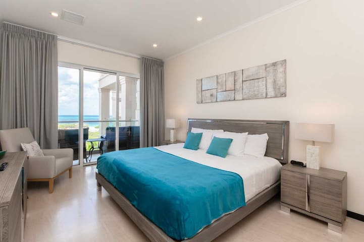Master bedroom with king-size bed, access to the balcony, and stunning views