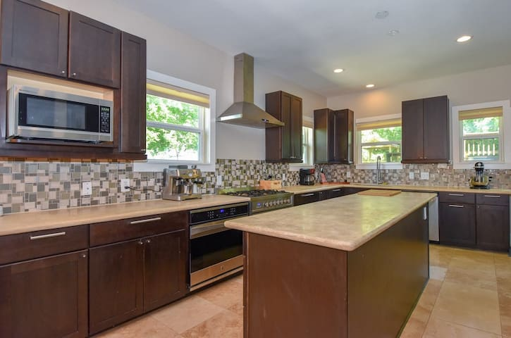 Chef's kitchen is outfitted with beautiful travertine stone, designer backsplash, 9-foot island, gas stove,  second convection oven, microwave, dishwasher and all the accouterments to make a gourmet meal.