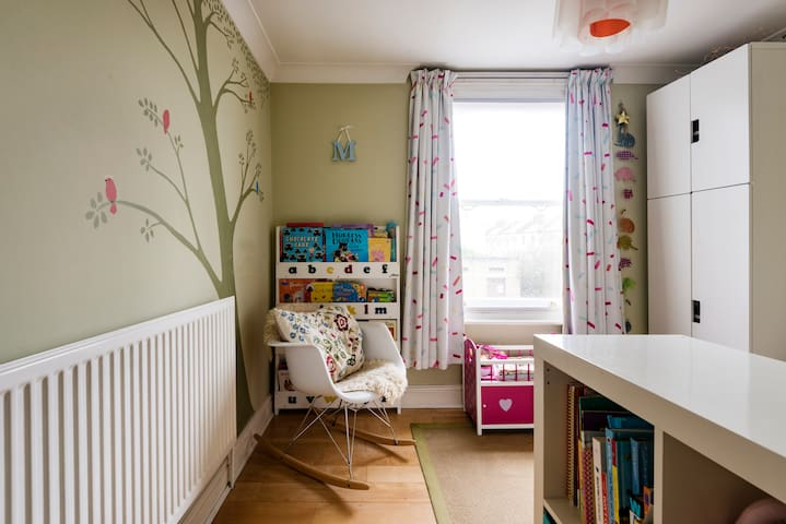 Children's bedroom with toddler bed, wardrobe, storage and toys and books to borrow. Lovely leafy outlook onto garden and canal.