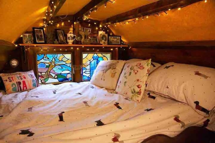 The double bed lit by a handmade stained glass windows that open to a view of the orchard