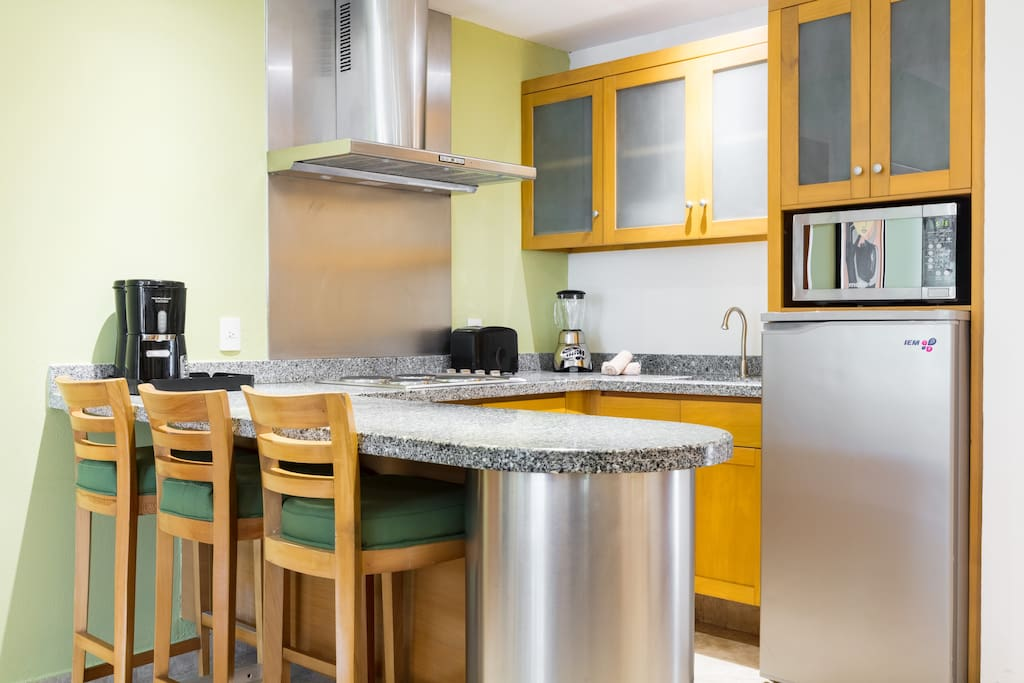 The kitchen includes a blender, microwave, mini-fridge, stovetop, dishwasher, cookware, and dishes.