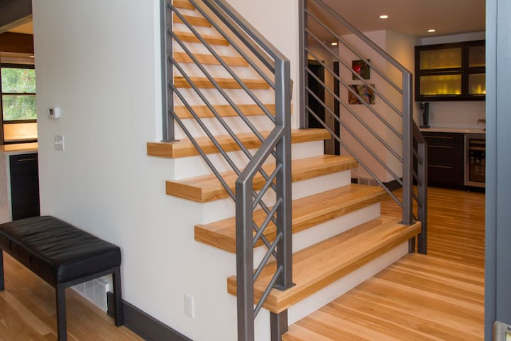 Entryway with open stairs connecting living room and dining room.